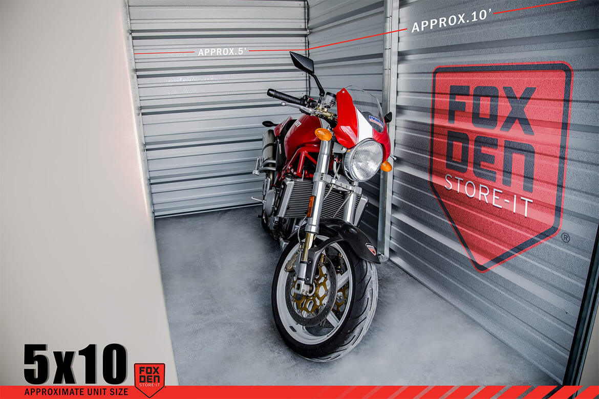 View of open storage unit with motorcycle inside